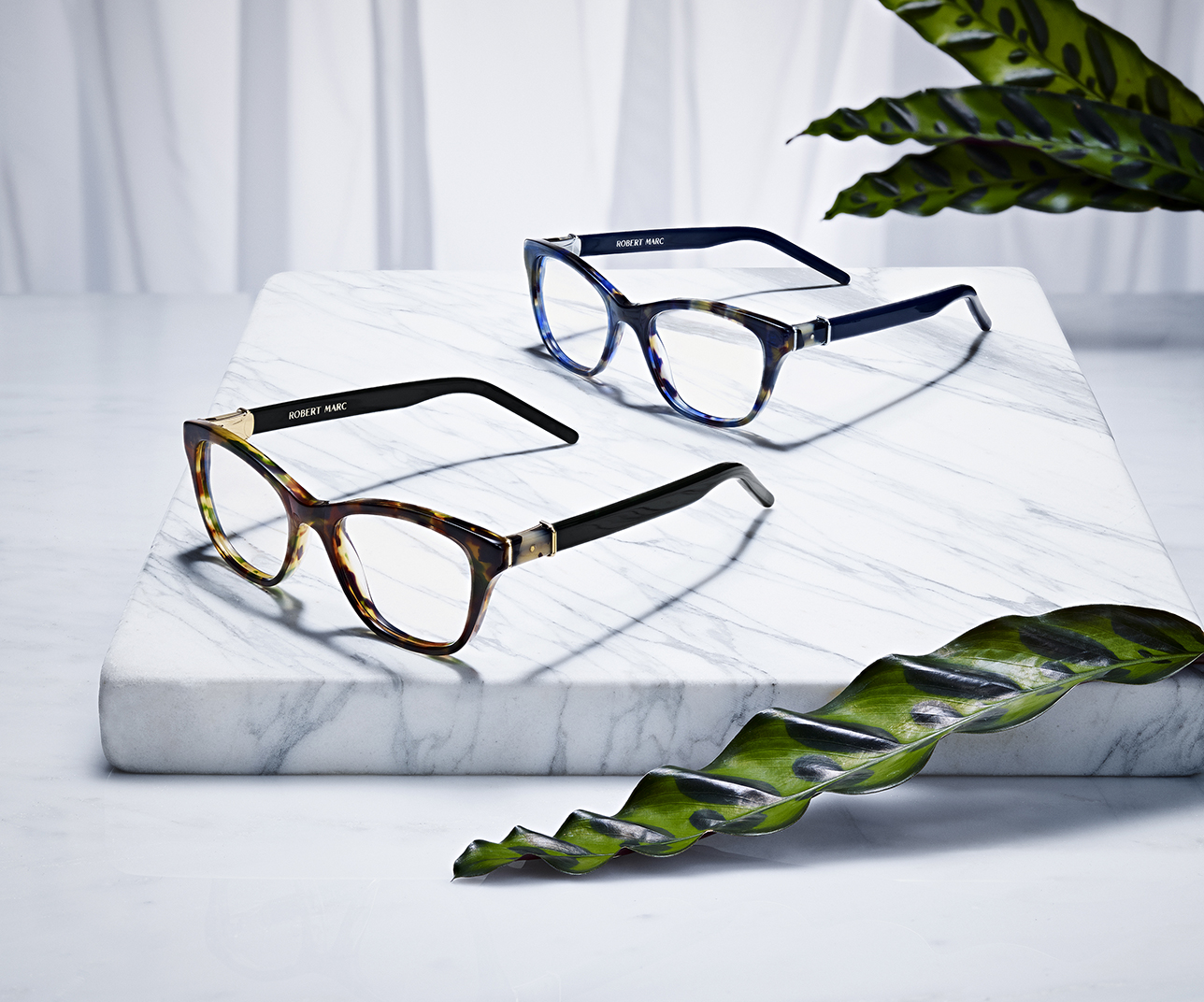 SUNGLASSES AND EYEWEAR BY ROBERT MARC SHOT ON MARBLE WITH PLANTS BY DAVID FILIBERTI