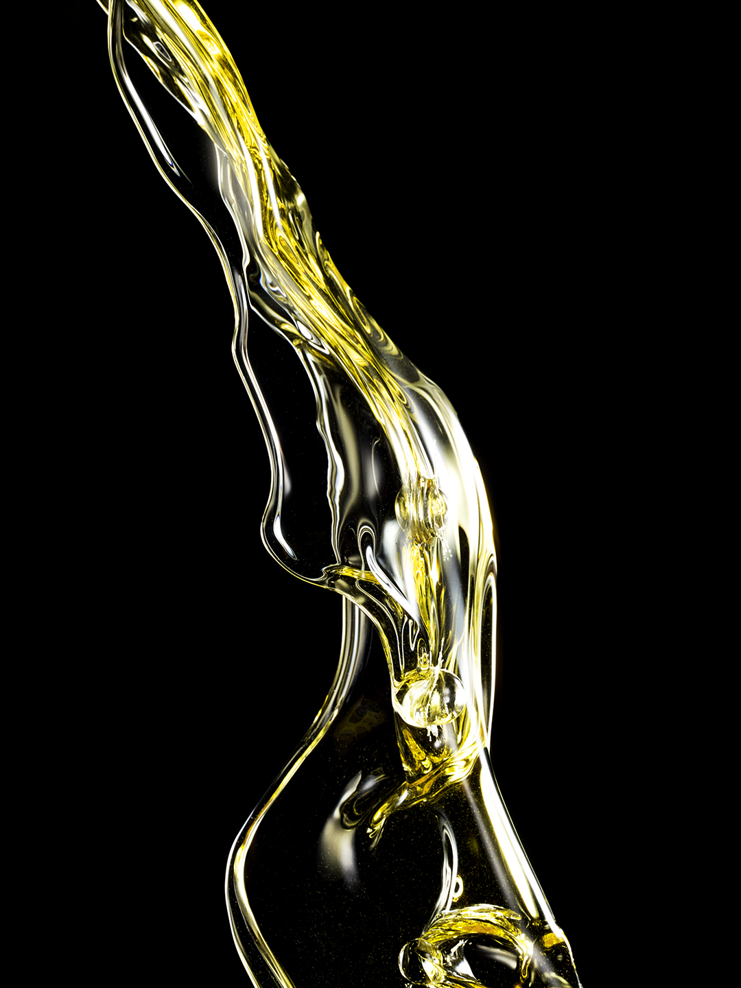 PROPRIETARY YELLOW LIQUID SHOT IN MID AIR CREATING ABSTRACT SHAPES SHOT BY DAVID FILIBERTI