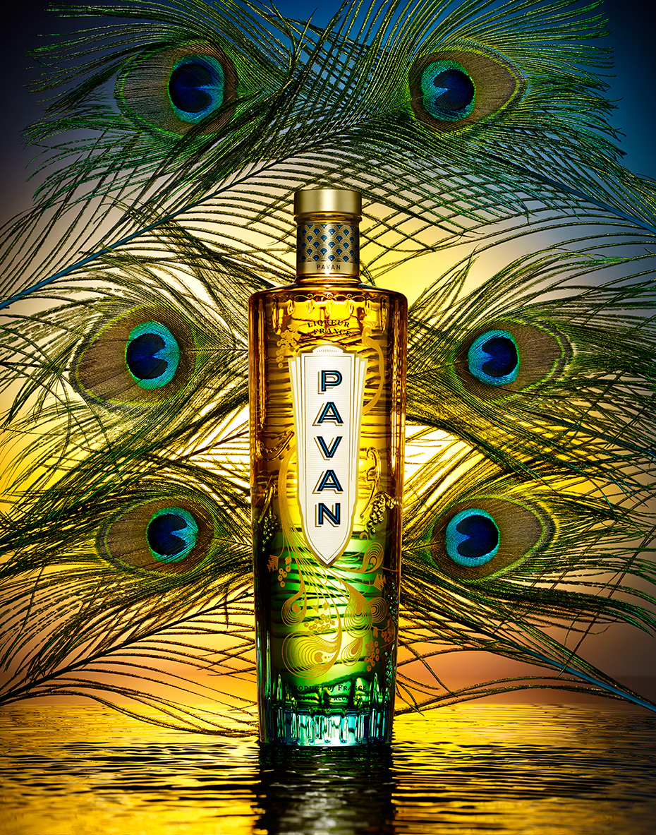 FRENCH LIQUOR PAVAN BOTTLE ON A SUNSET COLORED BACKGROUND WITH PEACOCK FEATHERS SHOT BY DAVID FILIBERTI