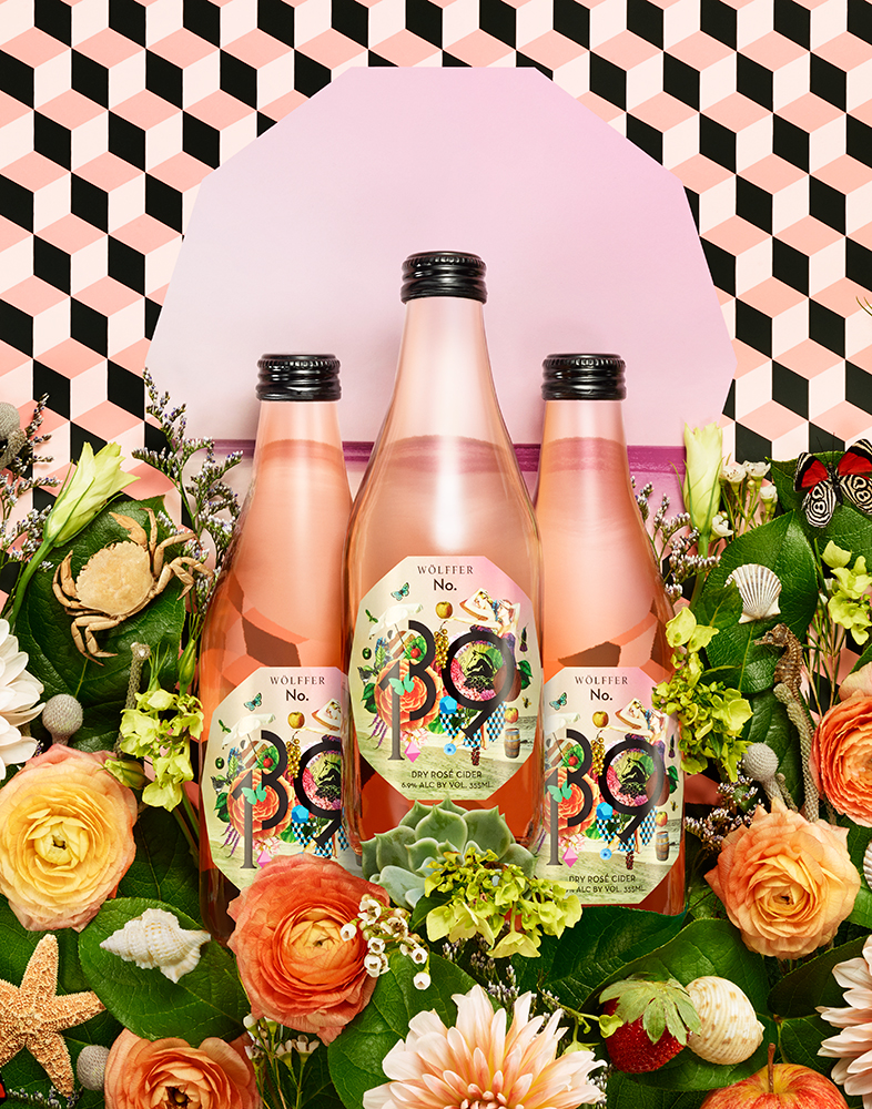 THREE ROSE CIDER BOTTLES ON GEOMETRIC PATTERNED BACKGROUND SURROUNDED BY SUMMER THEMED FLOWERS SHOT BY DAVID FILIBERTI