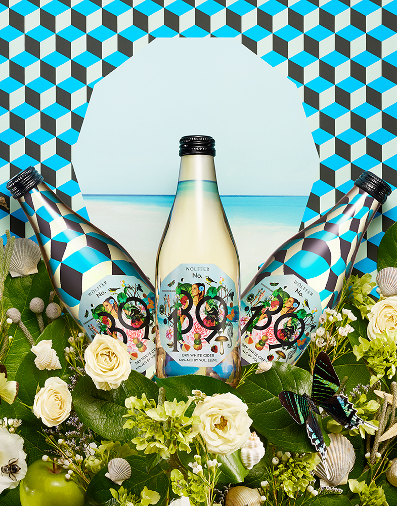 THREE WHITE CIDER BOTTLES ON GEOMETRIC PATTERNED BACKGROUND SURROUNDED BY SUMMER THEMED FLOWERS SHOT BY DAVID FILIBERTI