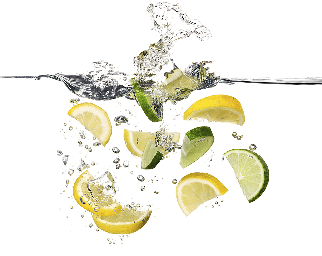 LEMON AND LIME WEDGES SPLASHING INTO WATER SHOT BY DAVID FILIBERTI