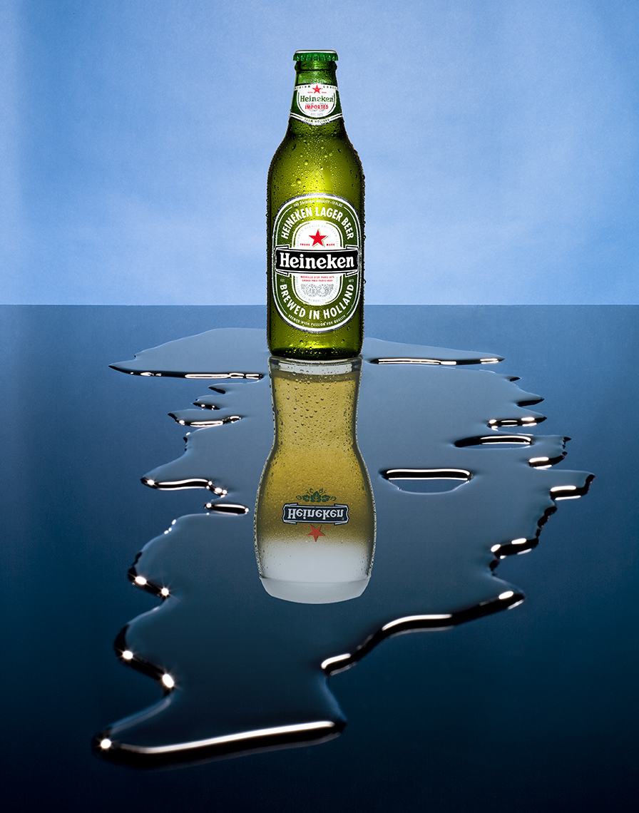 BEER BOTTLE WITH A BEER MUG REFLECTION AND A SPILL OF WATER SHOT BY DAVID FILIBERTI
